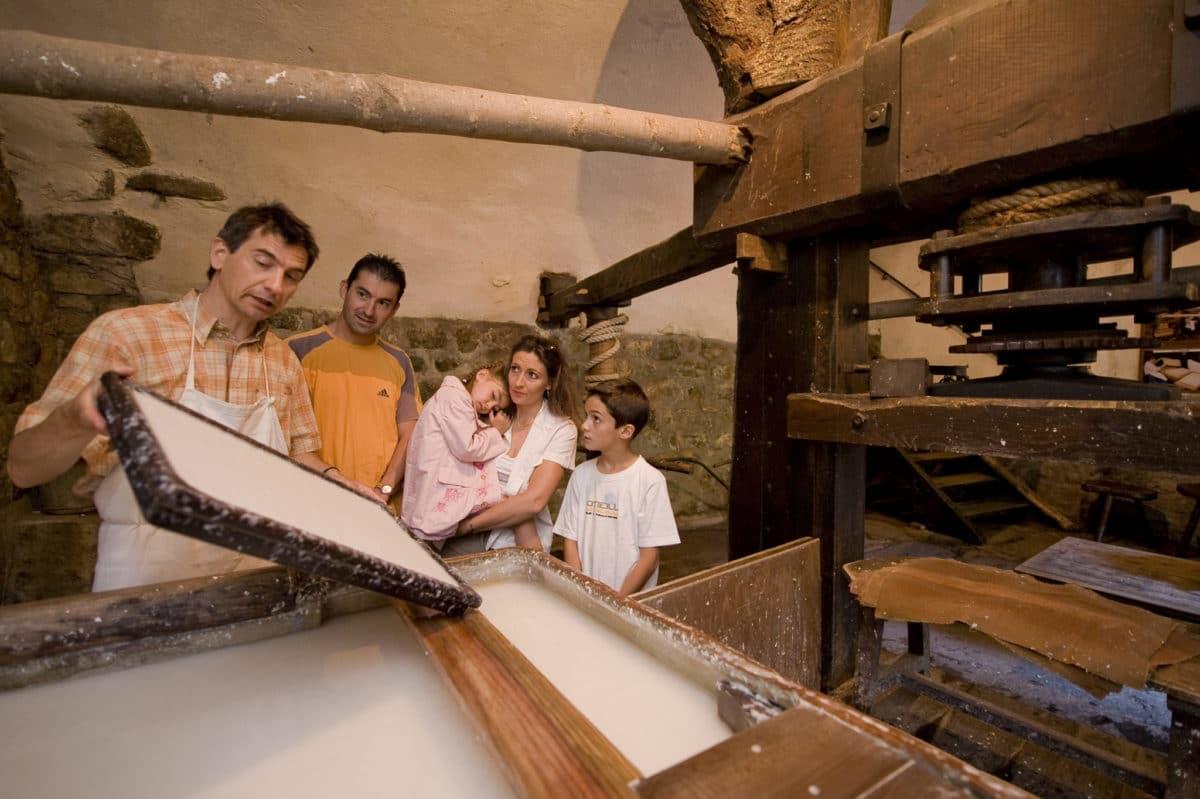 Photo d'un papetier présentant à une famille la cuve et la planche à papier