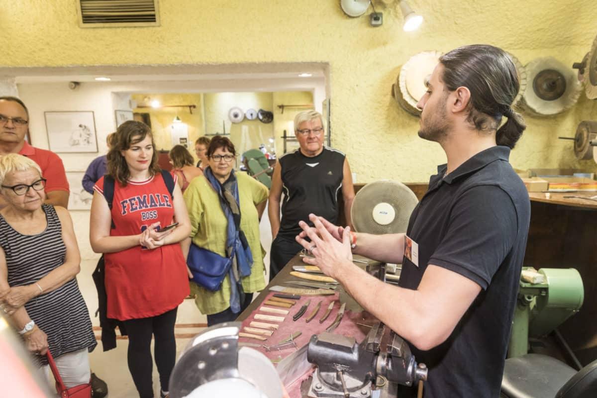 Coutelier d'art expliquant son savoir-faire à un groupe