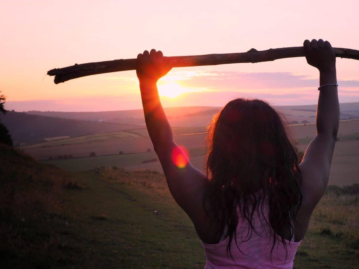 Photo d'une femme de dos levant les bras et face à un coucher de soleil