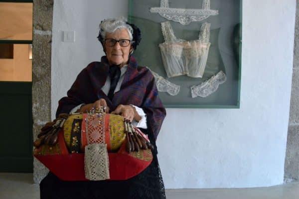 Photo de Ginette BRAVARD en tenue de dentellière traditionnelle, assise, avec le carreau de dentelle posé sur ses genoux
