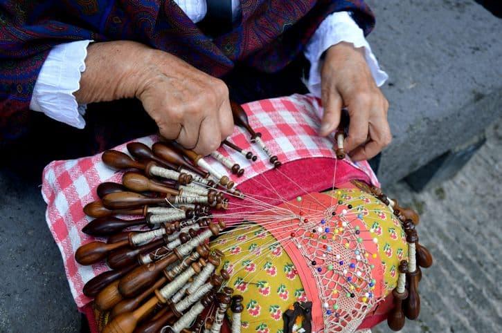Photo des mains de Ginette BRAVARD faisant une démonstration de création de dentelle : un savoir-faire très spectaculaire avec de nombreux fuseaux entremêlés